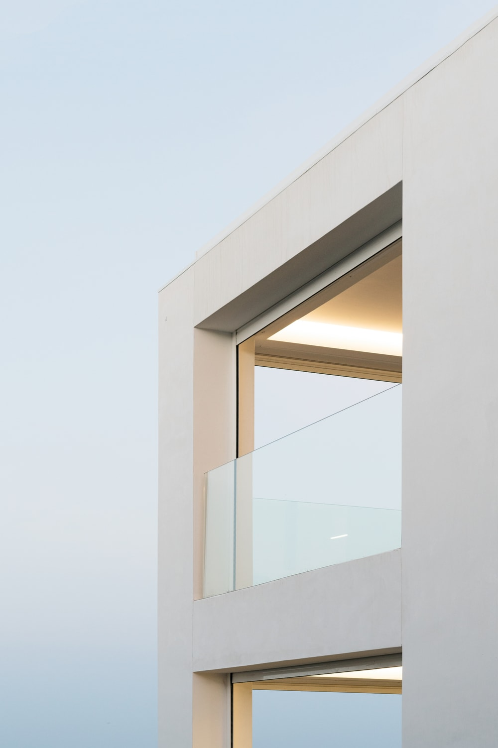 The second-floor balcony has lovely low glass walls to serve as railings in order to maximize the view and provide safety as well.