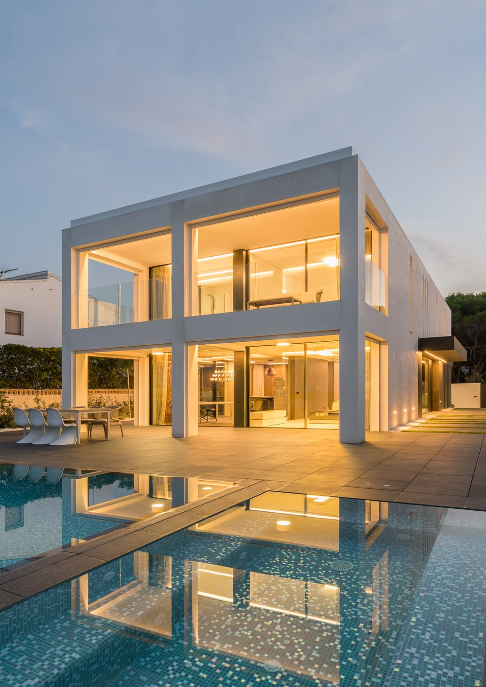 You can clearly see the different sections of the interiors of the house from the back through the large glass walls. These really go well with the white exteriors of the house.