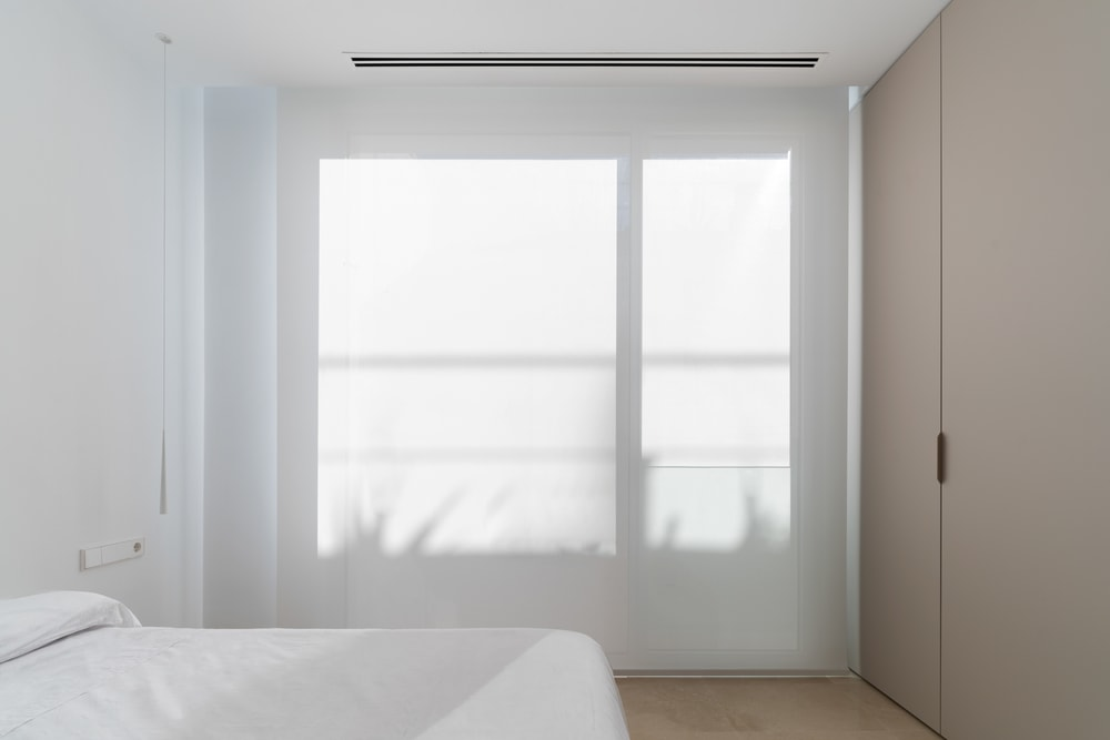 This is the simple and minimalist bedroom with a white bed that matches the white walls and ceiling. These are then complemented by the floor and the wall of wooden cabinets.