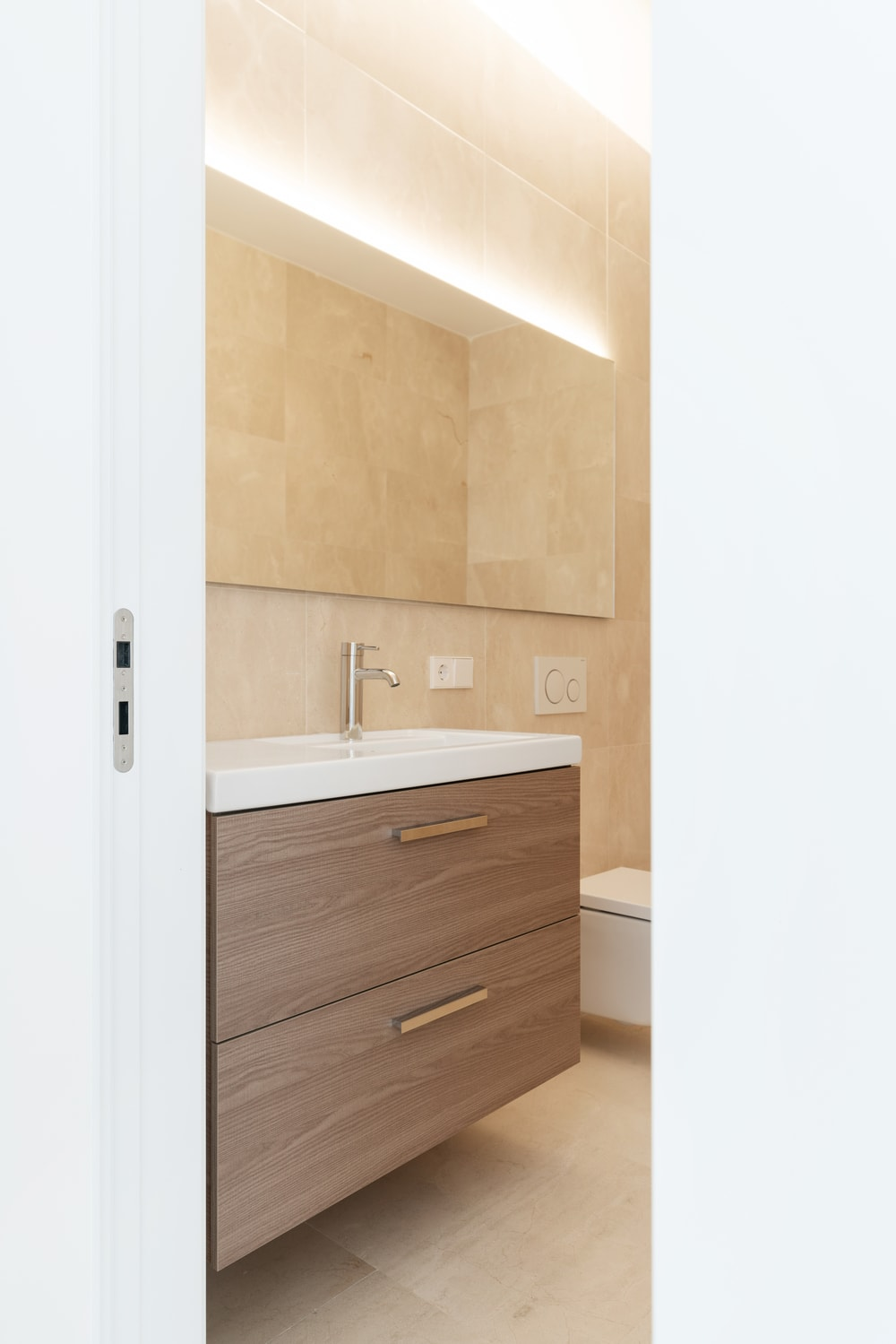 This other bathroom has a white sliding wooden door that opens up to the vanity beside it. This is followed by the toilet that stands out against the beige marble walls.