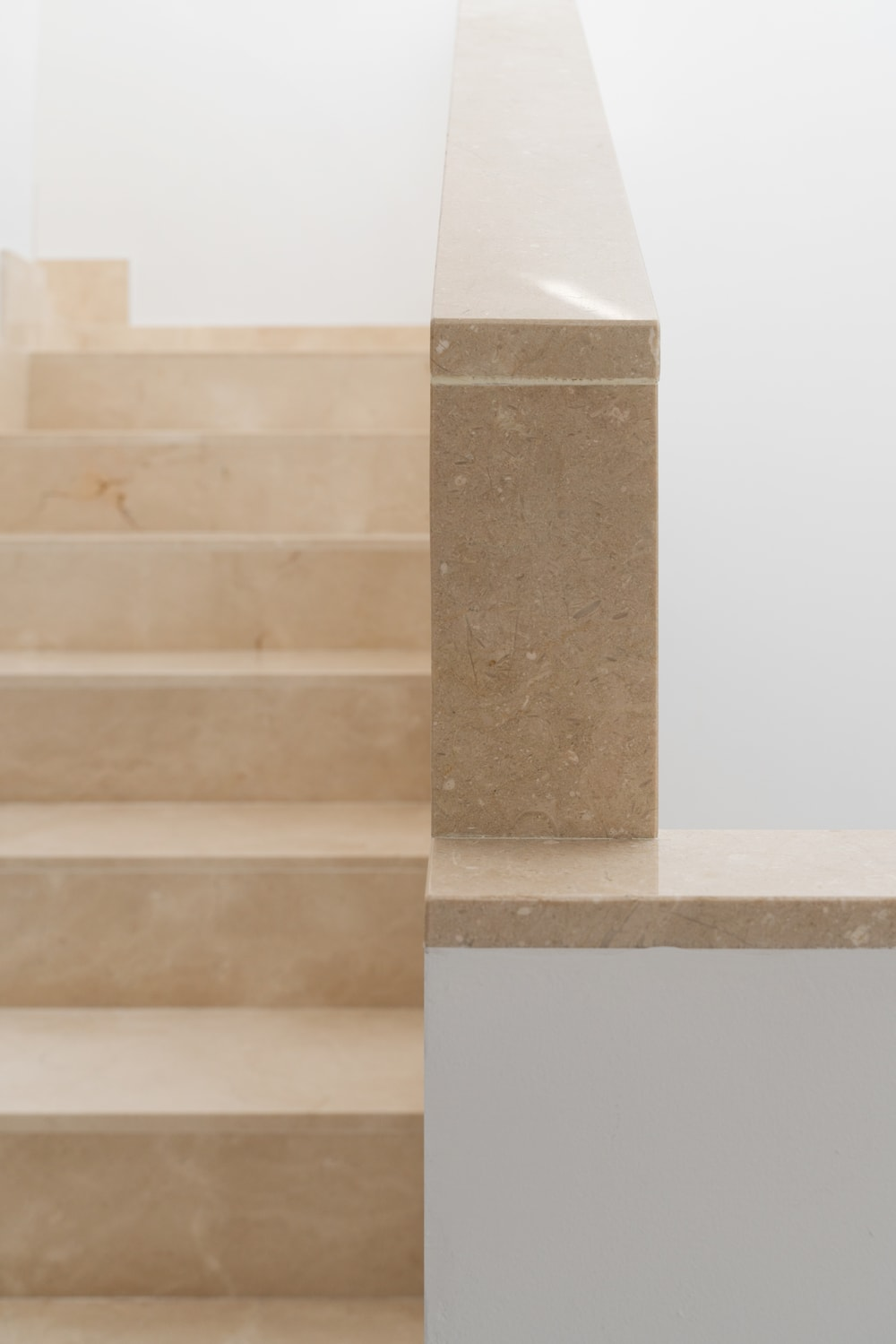 This is a close look at the beige marble steps of the staircase. It's material is also used on the banisters bordering the sides of the stairs to complement the white walls.