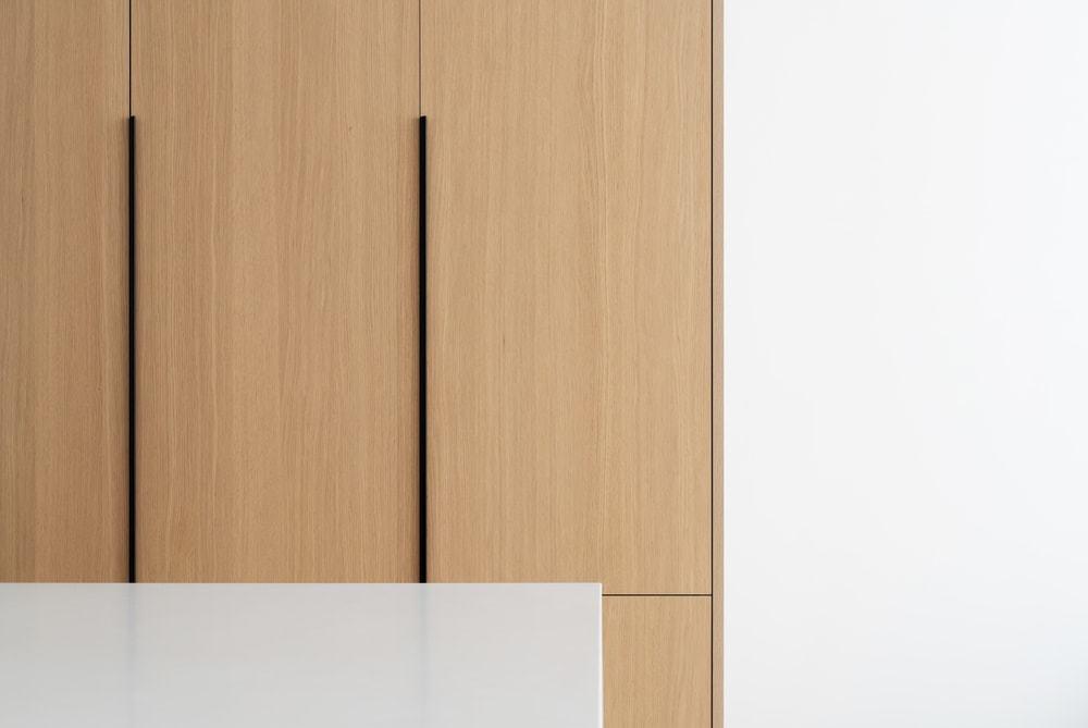 This is a part of the large wooden structure of the kitchen beside the sofa and kitchen island. This has built-in cabinets with a modern design.