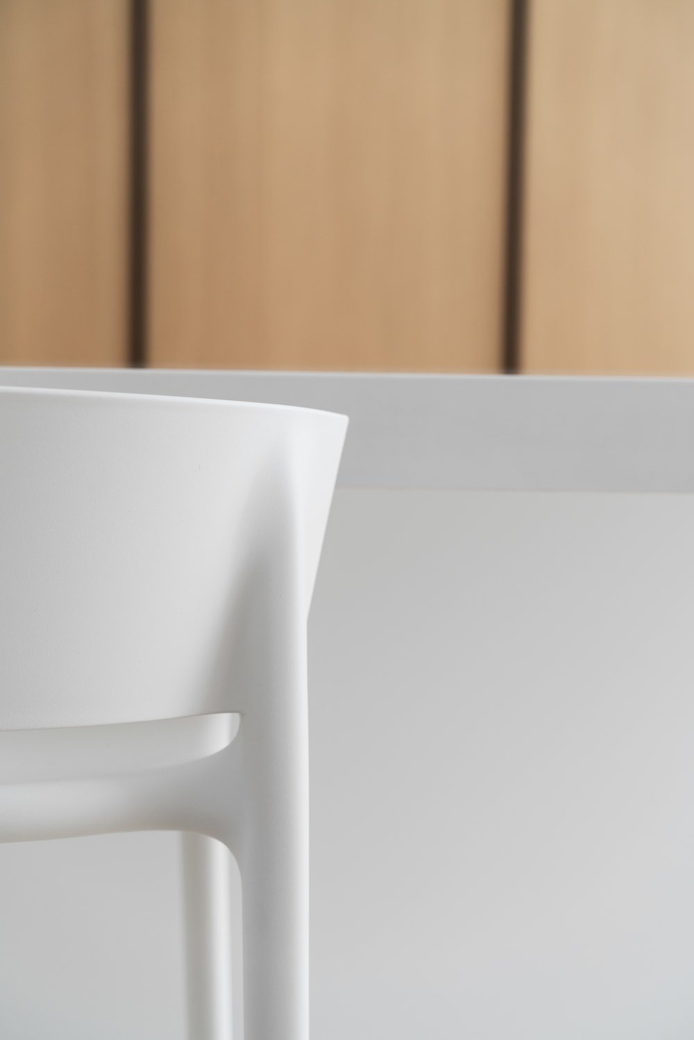 This is a close look at one of the modern white stools of the kitchen that totally blends in with the breakfast bar.