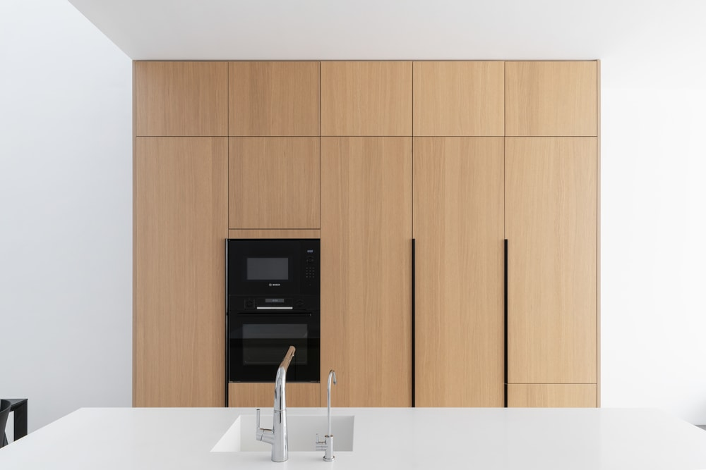This angle shows the whole countertop of the kitchen island. It stands out against the black modern appliances of the large wooden structure across from the sink area.