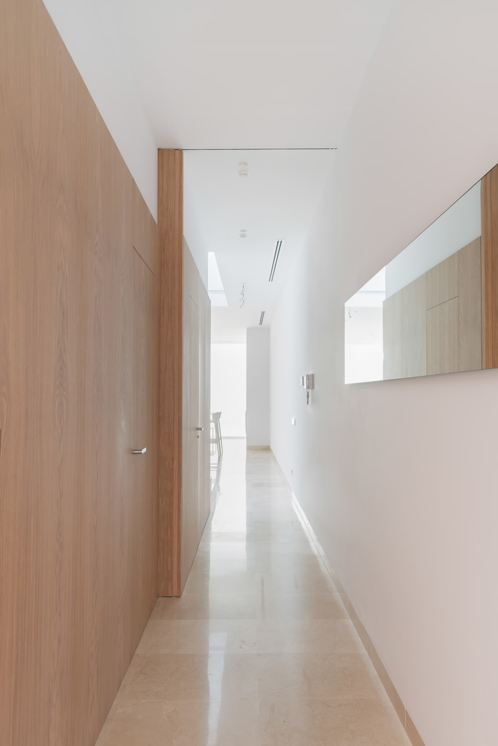 This is the hallway of the house with a lovely wooden sliding door in the middle to match the sliding panel of the window on the side of the hallway.