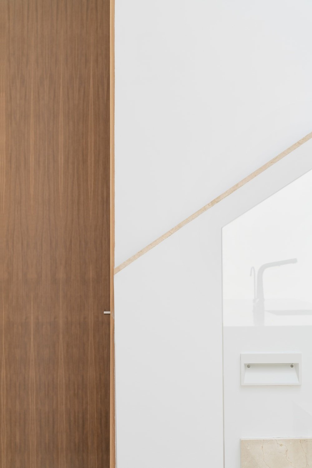 This close up look at a corner of the house appears as if a piece of modern art showing the lovely aesthetic of the house filled with white and wooden tones.