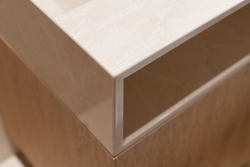 This close up inspection of the bathroom countertop features its beige marble countertop that extends to the built-in shelf facing the bathroom.