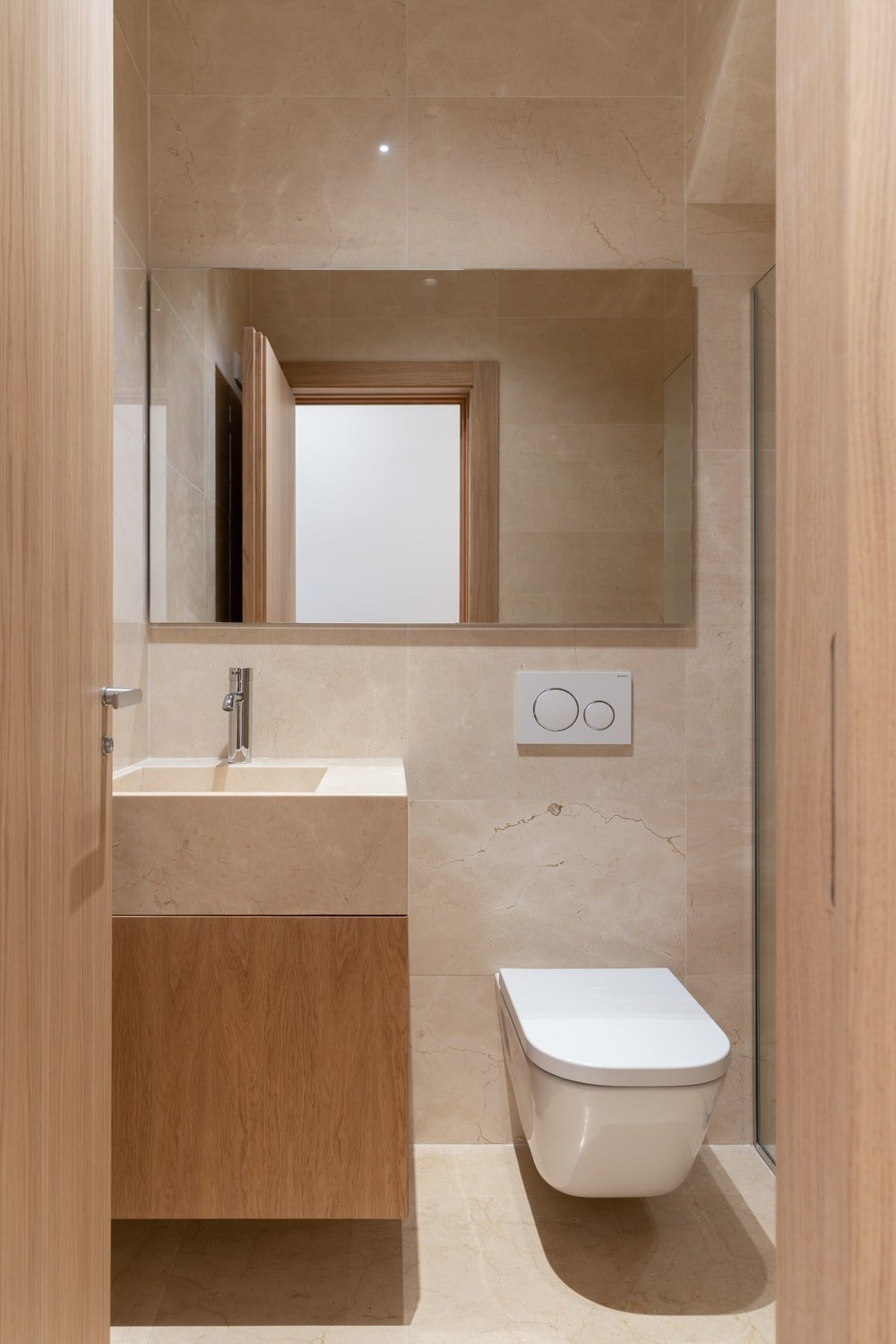 This is charming and simple bathroom with a white modern toilet to match the sink housed in a wooden vanity. This toilet is topped with a large wall-mounted mirror.
