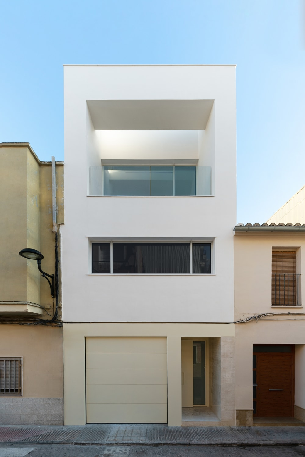 This front look at the house showcases its clean and white exterior walls complemented by the glass walls and balcony.