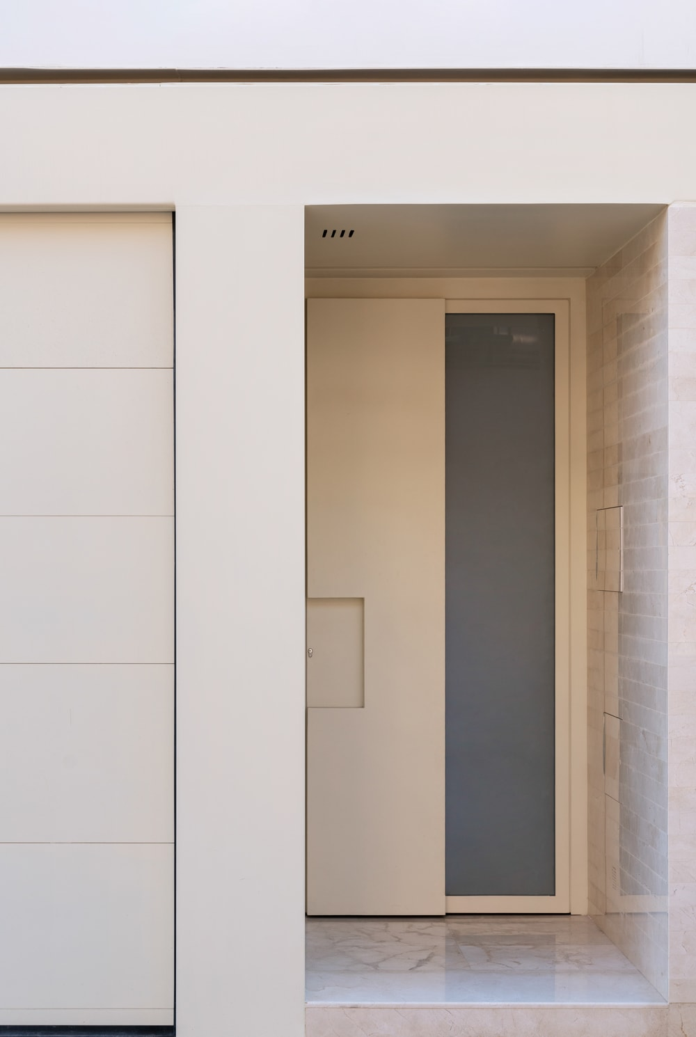 The main door has a light wooden tone adorned with a tall and thin glass panel on the side.