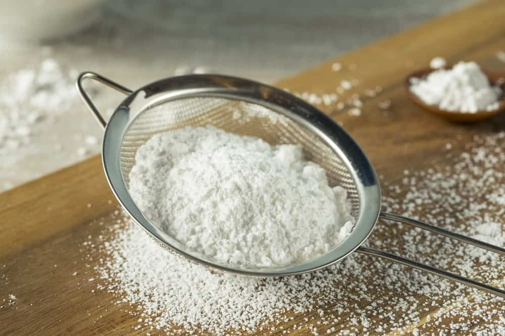 Confectioner's sugar being filtered by a strainer.