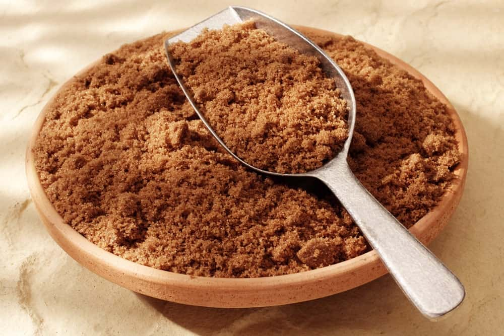 A wooden bowl of dark brown sugar with scoop.