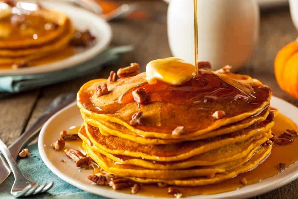 Pouring maple syrup on pancakes