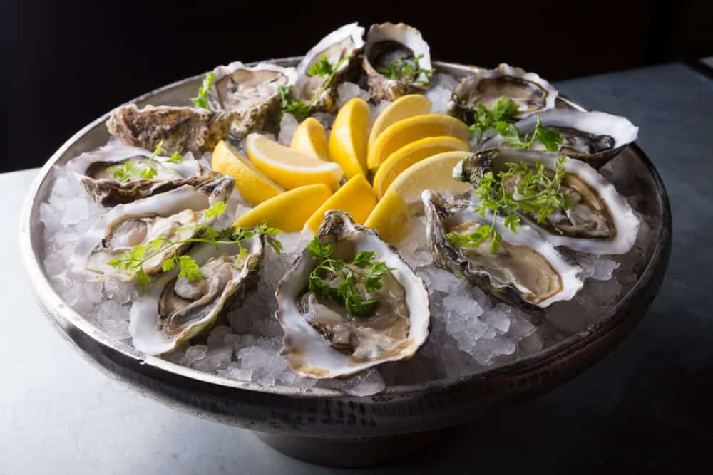 A plate of fresh oysters with lemon slices.
