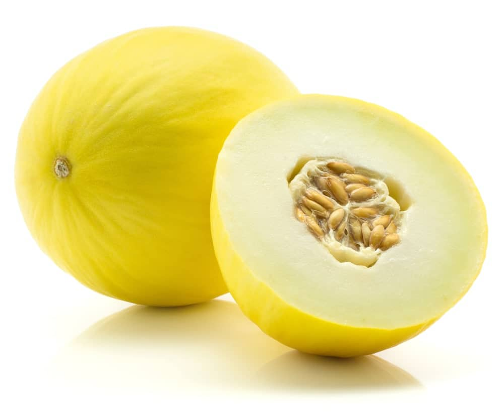 A whole and a half slice of Honeydew Melons