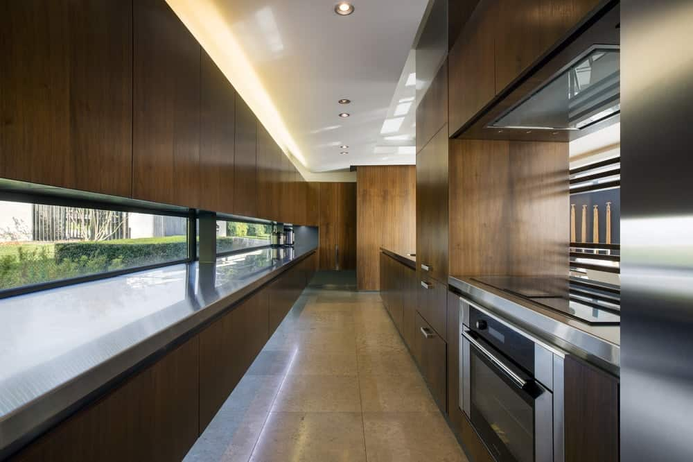 This is a long and narrow kitchen with dark brown wooden modern cabinetry to house the modern stainless steel appliances. These dark elements are complemented by the ceiling and the row of windows.