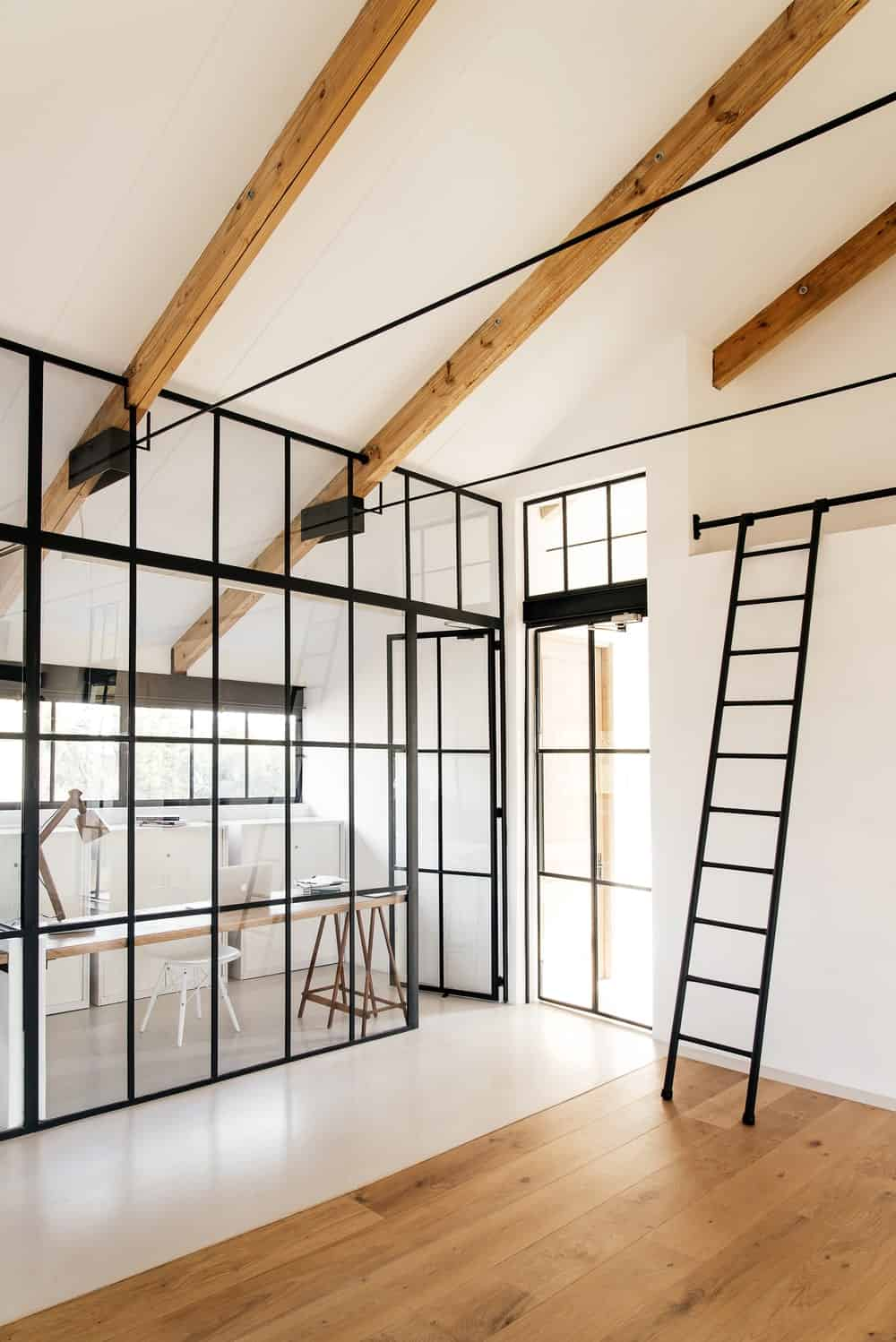 This is a simple and homey office with bright white walls and large ceiling with exposed beams. These makes the black frames of the glass wall stand out along with the glass window behind the desk.