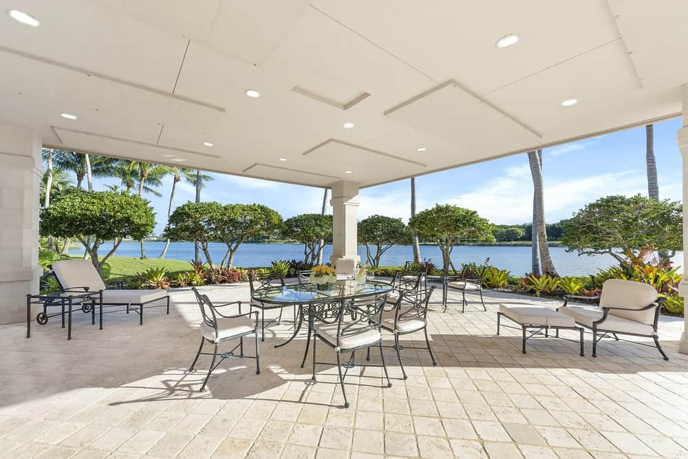 This is the flawlessly covered patio with a tall designed white roof with recessed lights. This is supplemented by outside tiles and open walls.