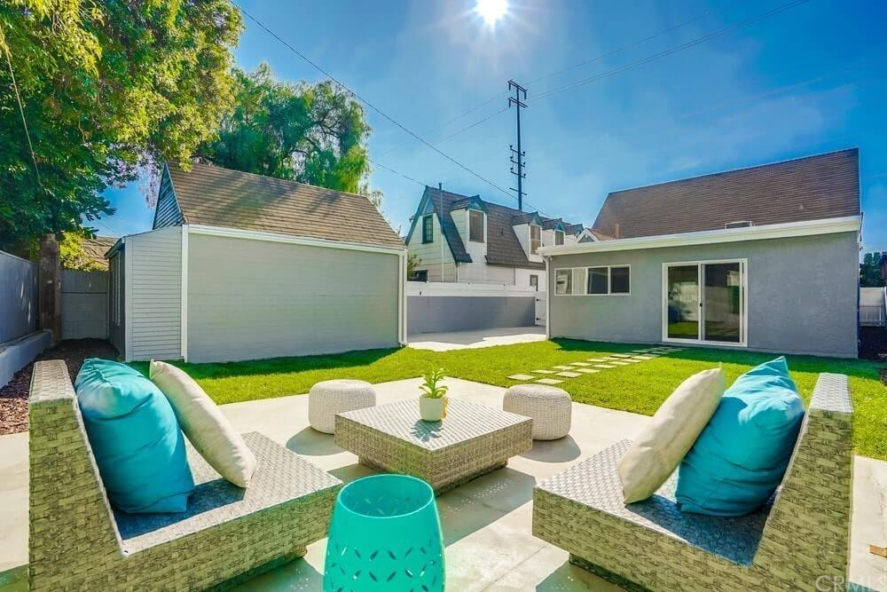 This stunning section of the backyard features a cozy sofa with a stylish trash can on the side and a coffee table in the middle.