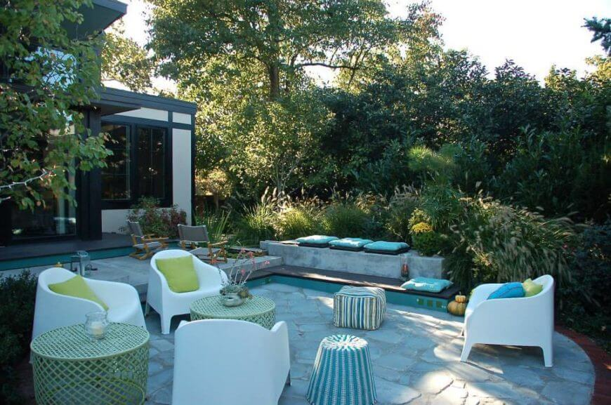 The back patio shares a large group of novel seating alternatives, with white easy chairs and wicker tables tucked away in rich greenery behind the home.