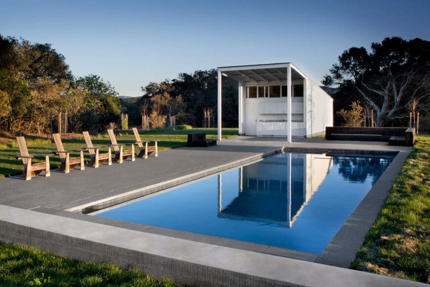 The extensive patio and pool area plays host to an enormous pool house, worked in a similar moderate style as the barn home.