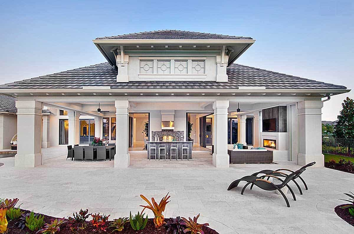 This covered patio features an outdoor living area and an outdoor dining area. It has a dining table set and a comfy sofa set in front of the fireplace.