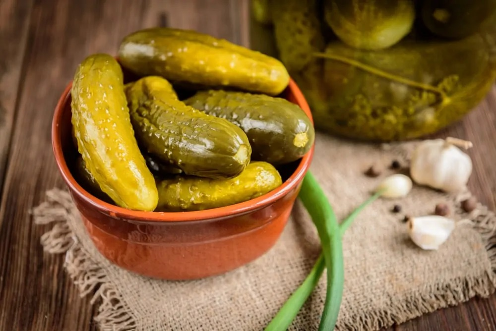 A small bowl of fresh pickles on a rustic background.