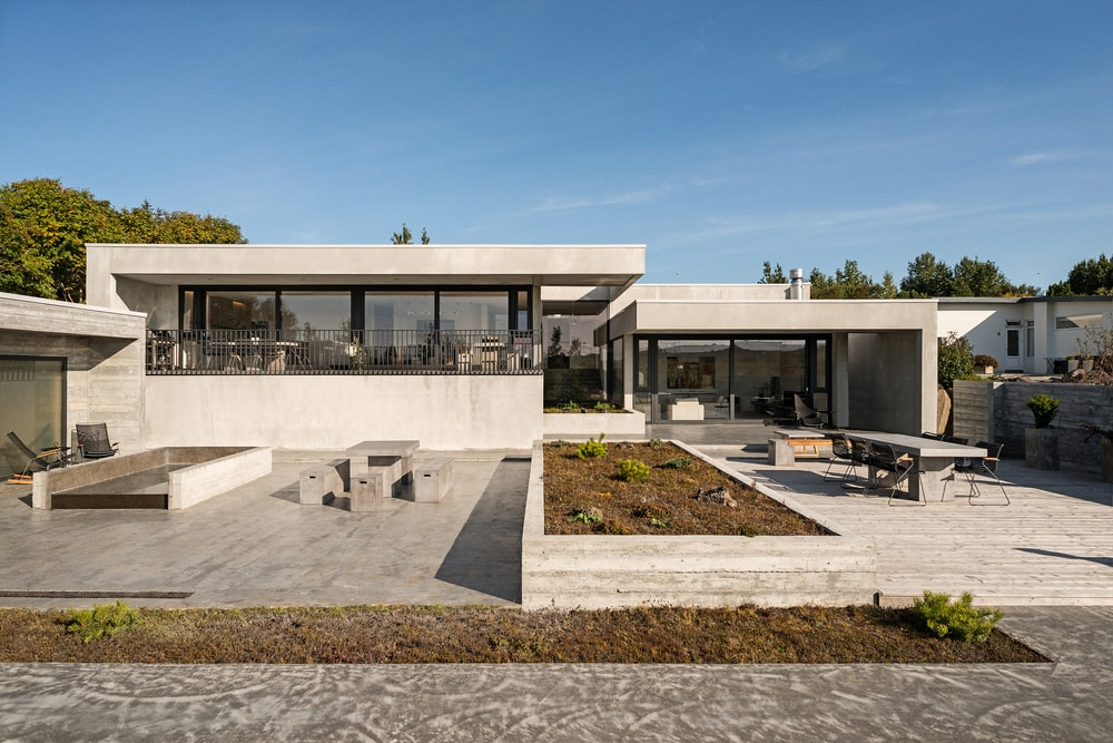 This view of the house features the large patio fitted with sitting area on one side and a stone dining set on the other side of the large planter. This whole area has a lovely concrete floor edged with a narrow patch of soil ready for any plants.