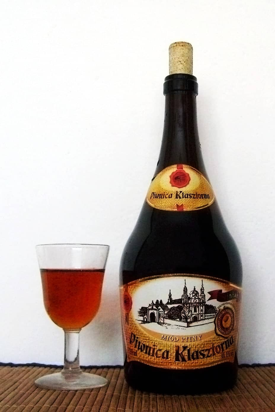 A bottle of medium-dark Trojniak mead made from one part honey and two parts water.