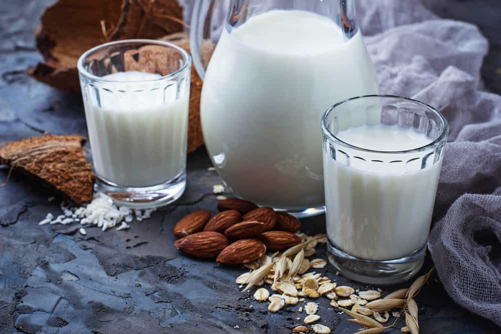 A jar of milk between two glass of milk surrounded by various nuts and a cloth gauze.