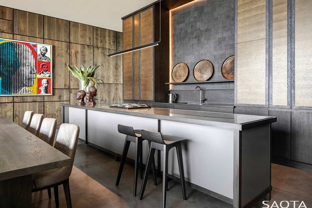 This is a sophisticated and luxurious long and narrow kitchen with a sleek dark gray countertop to its large kitchen island paired with dark stools for the breakfast bar beside the dining area.