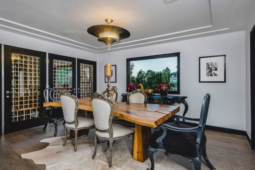 The rustic wooden dining table of this dining room is complemented by the black chairs, black window frames and the black console table that stands out against the white walls and ceiling.