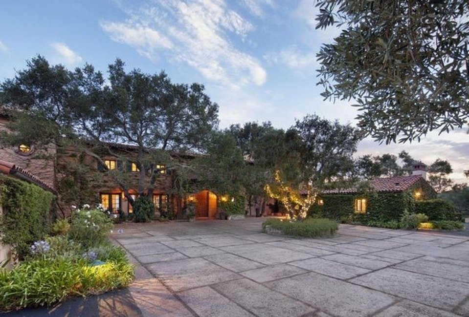 This is the front view of the house with a large concrete courtyard adorned with lovely landscaping of tall trees and shrubs warmed by the rope lights and the lights from the windows. Images courtesy of Toptenrealestatedeals.com.