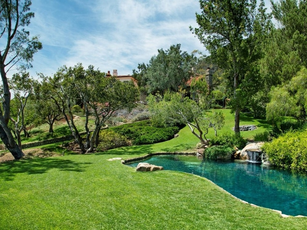 This is the beautiful pool of the house surrounded by lush grass lawns that transitions perfectly with the pool to create a seamless and natural look paired with cascading water. Images courtesy of Toptenrealestatedeals.com.