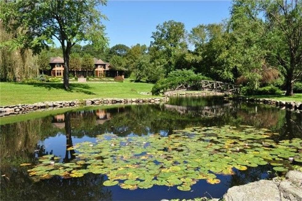 This is a view of the house that showcases the beautiful pond that sets a beautiful scene along with tall trees and lush grass lawns to complement the house in the distance. Images courtesy of Toptenrealestatedeals.com.