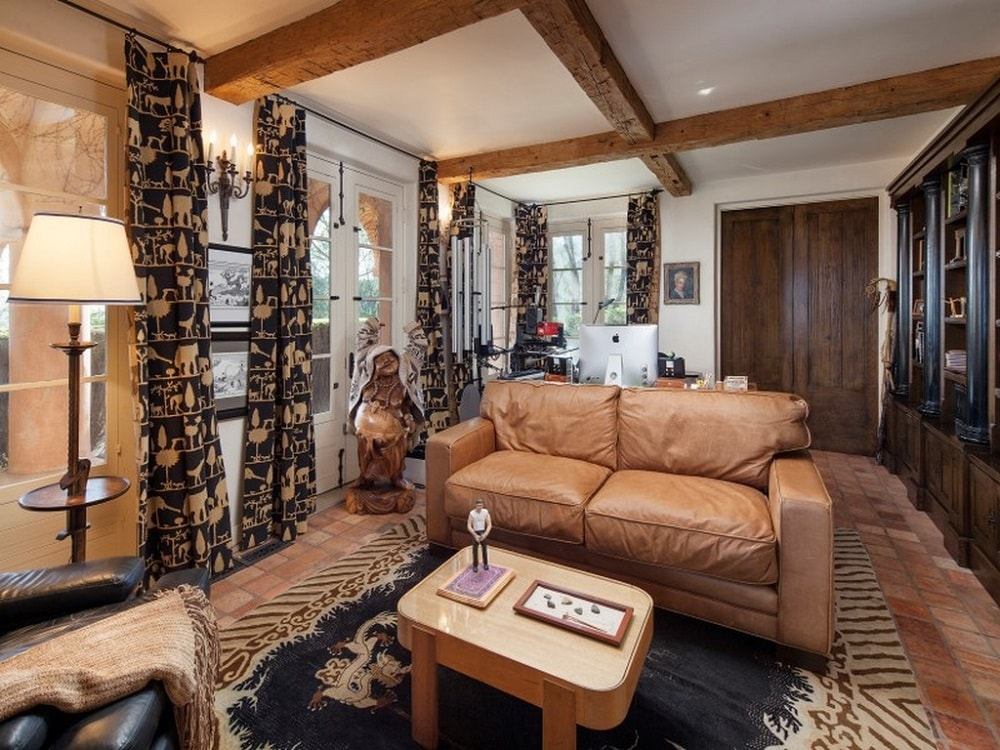This is a charming and intimate living room with a beige ceiling that has exposed wooden beams to match the wooden door and the brown leather sofa on the colorful patterned area rug. Images courtesy of Toptenrealestatedeals.com.