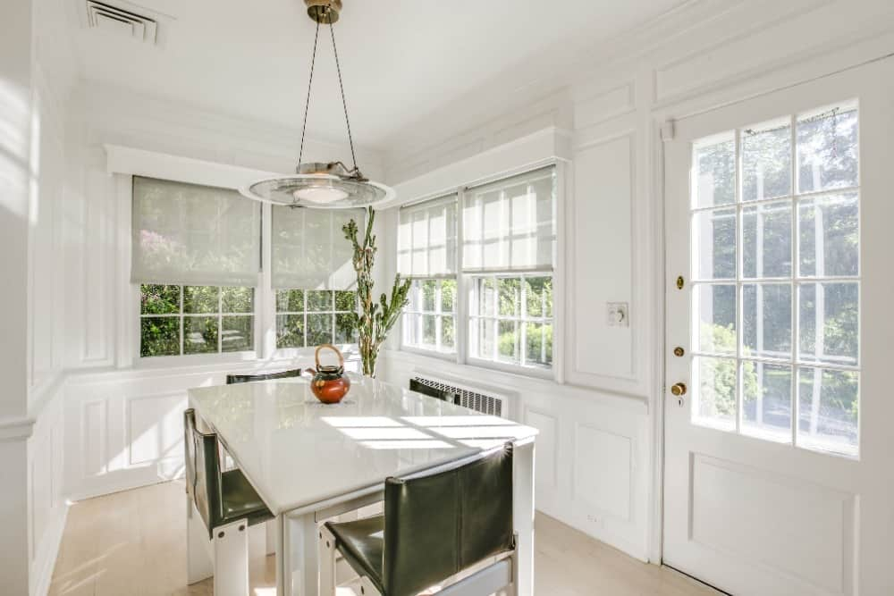 This charming dining room has white walls, ceiling and rectangular dining table. These are then contrasted by the black leather chairs.