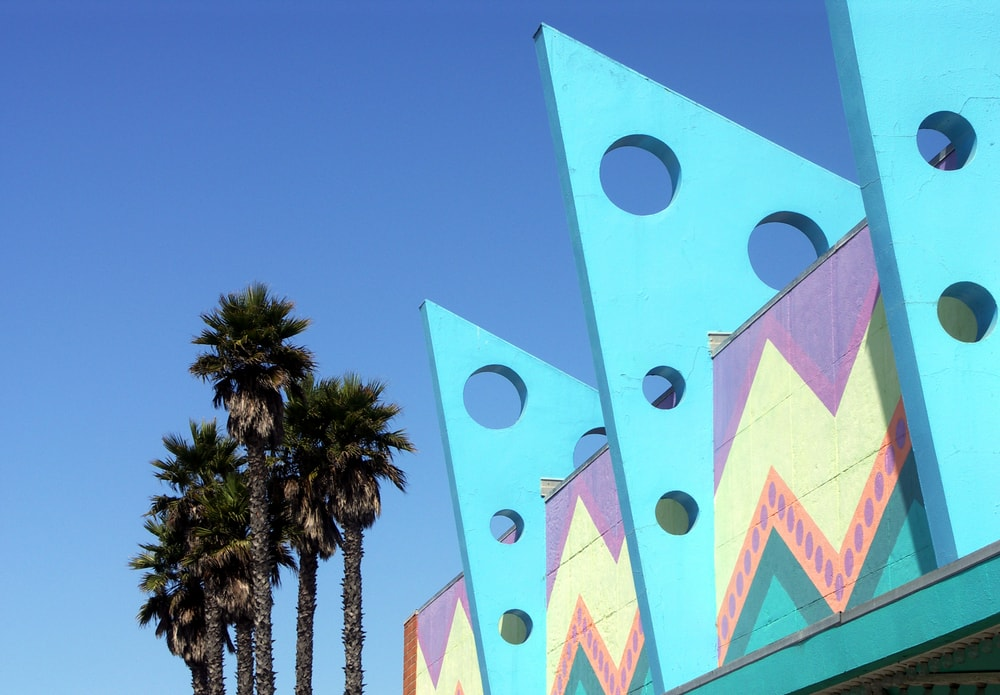 Art deco building and palm trees against a backdrop of clear blue sky.