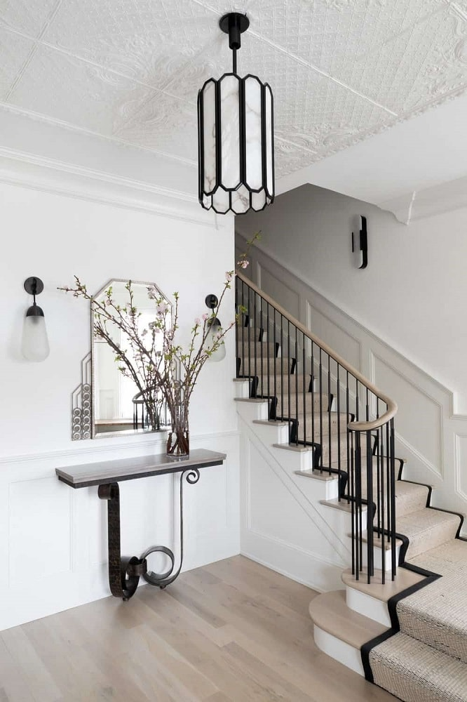 The various white surfaces of this simple foyer has differences when it comes to texture and patterns. These are then contrasted by the black semi-flush mount lighting, built-in console table and the wrought iron railings of the staircase.