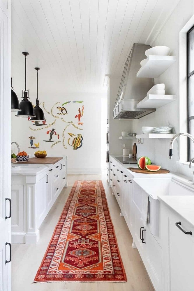 The long and narrow white flooring of this kitchen is adorned with a colorful patterned area rug to give a nice contrast to the bright white cabinetry and countertops. The kitchen island is then topped with a row of black pendant lights.