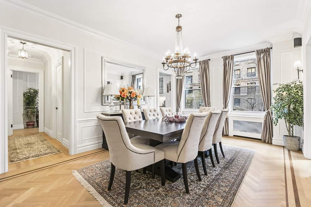 This is the bright dining room with white walls and ceiling contrasted by the black rectangular dining table and matching waist-high cabinet on the side topped with a mirror.