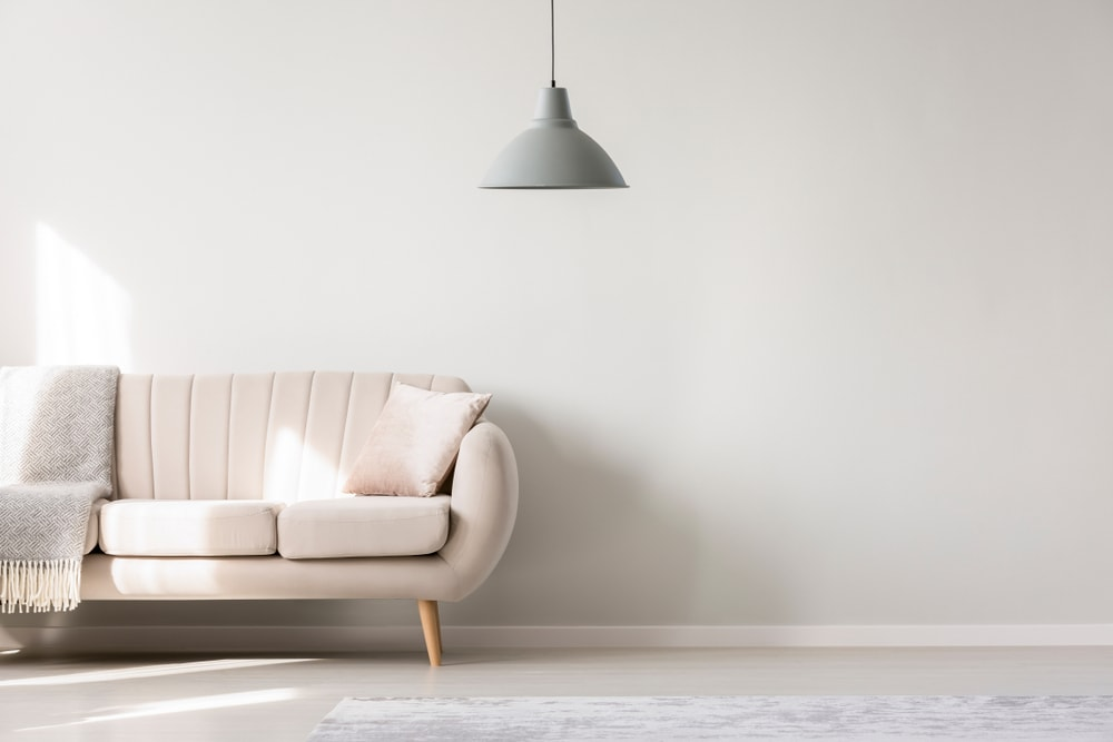 Cropped image of a beige sofa on an empty white living room.