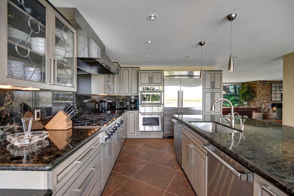 This is the galley-style chef's kitchen with dark granite countertops that pairs well with the stainless steel modern appliances. These are then complemented by the charming terracotta flooring tiles and white ceiling.