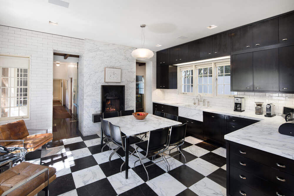 This dining area features black and white tiles and white marble top dining table paired with black chairs.