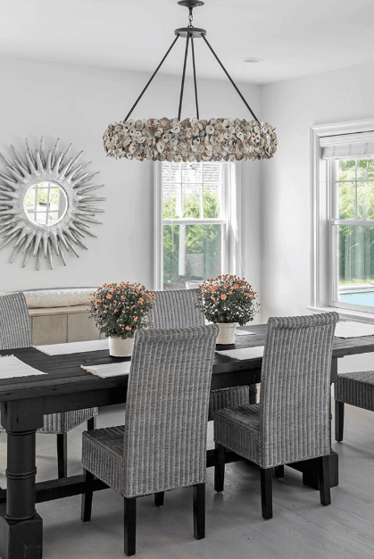This dining room features a black wooden dining table paired with cozy chairs and a stainless steel frame mirror.