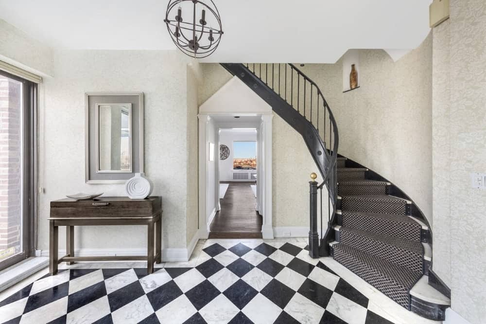 The enchanting and stylish foyer has checkered black and white flooring, a wooden comfort table, and a spiral staircase.