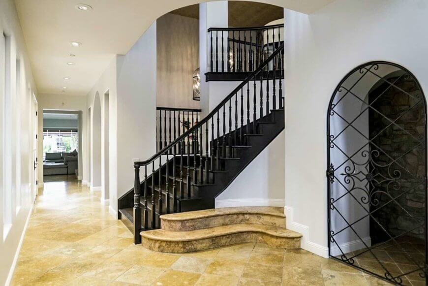 An entry hall featuring tiles flooring, white walls and a tall ceiling with lined up recessed lights. The hall leads to the living space while there's a path leading to the basement and there's a staircase as well.