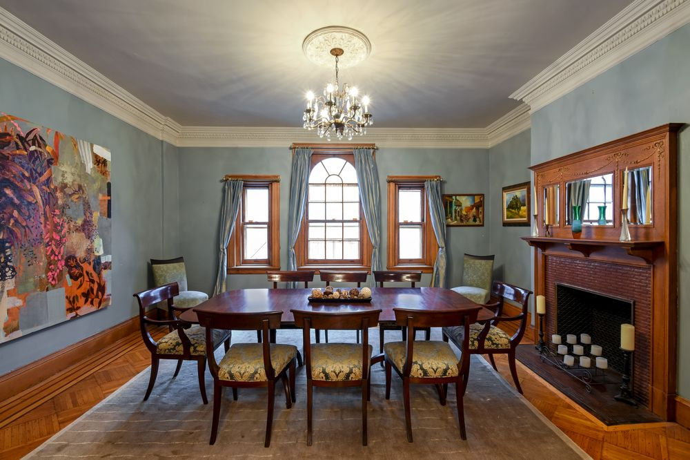 The elegant dining room has a large fireplace with a wooden mantle to stand out against the warm tone of the walls. This also makes the dark wooden dining set stand out illuminated by the arched windows. Images courtesy of Toptenrealestatedeals.com.