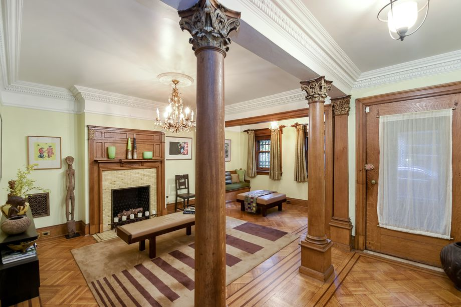 This is the view of the family room from the vantage of the hallway. Here you can see the beautiful hardwood flooring that matches with the wooden pillars that adorn the large entryway to the family room that is warmed by a large fireplace. Images courtesy of Toptenrealestatedeals.com.