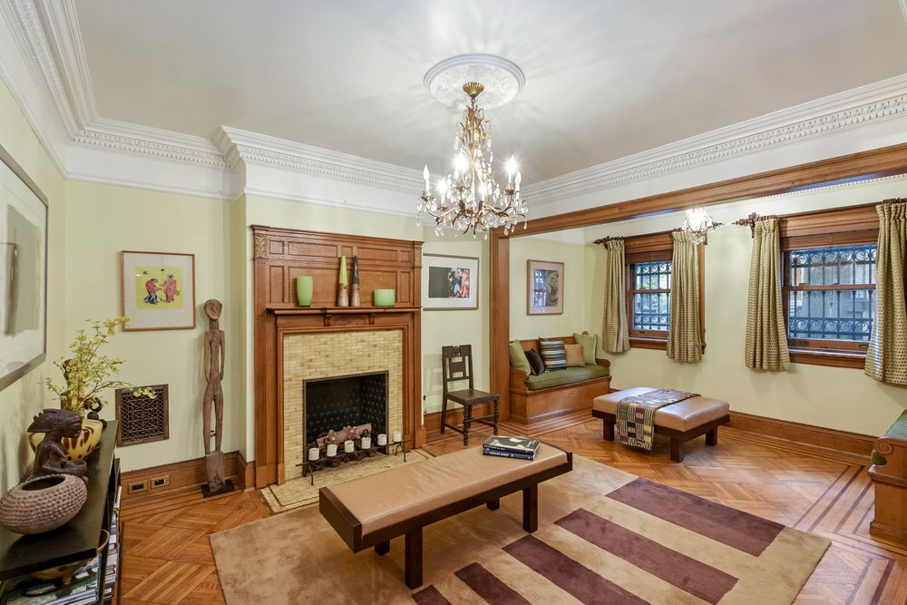 This is the family room with various sitting areas on the hardwood flooring. This matches well with the mantle of the fireplace topped with a majestic chandelier. Images courtesy of Toptenrealestatedeals.com.